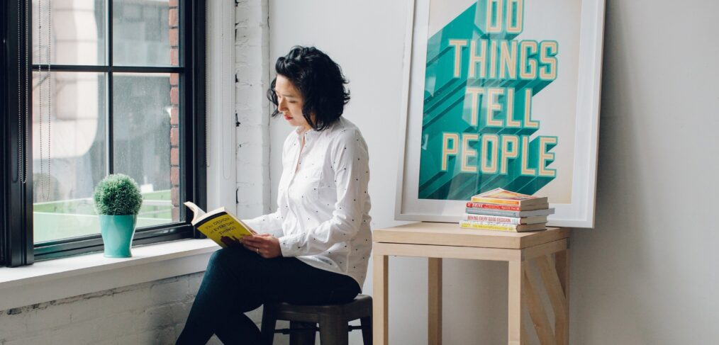 Women sitting next to sign that says 'Do Things. Tell People' to show personal branding