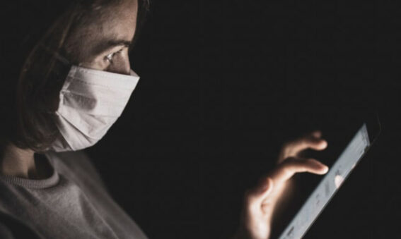Woman with mask using ipad
